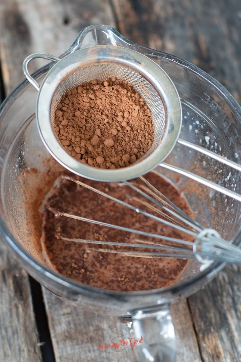 sifting cocoa powder into icing
