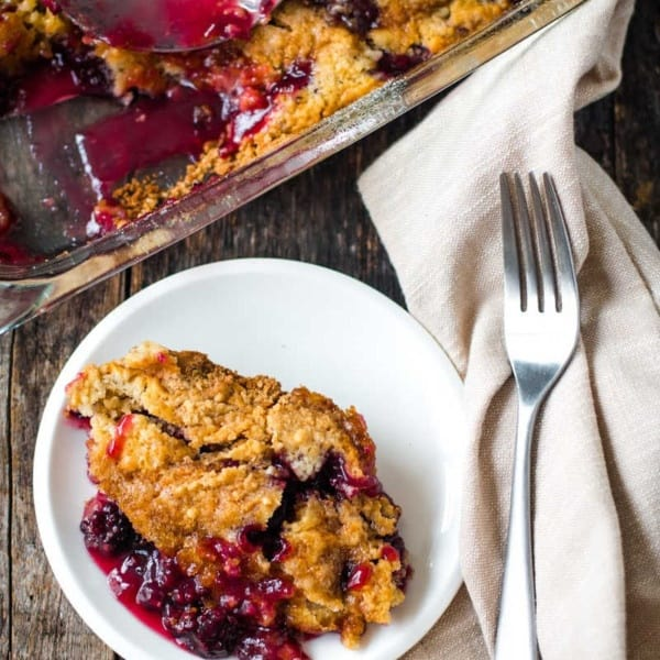 Blackberry Dump Cake vertical image with full pan of cake in the background