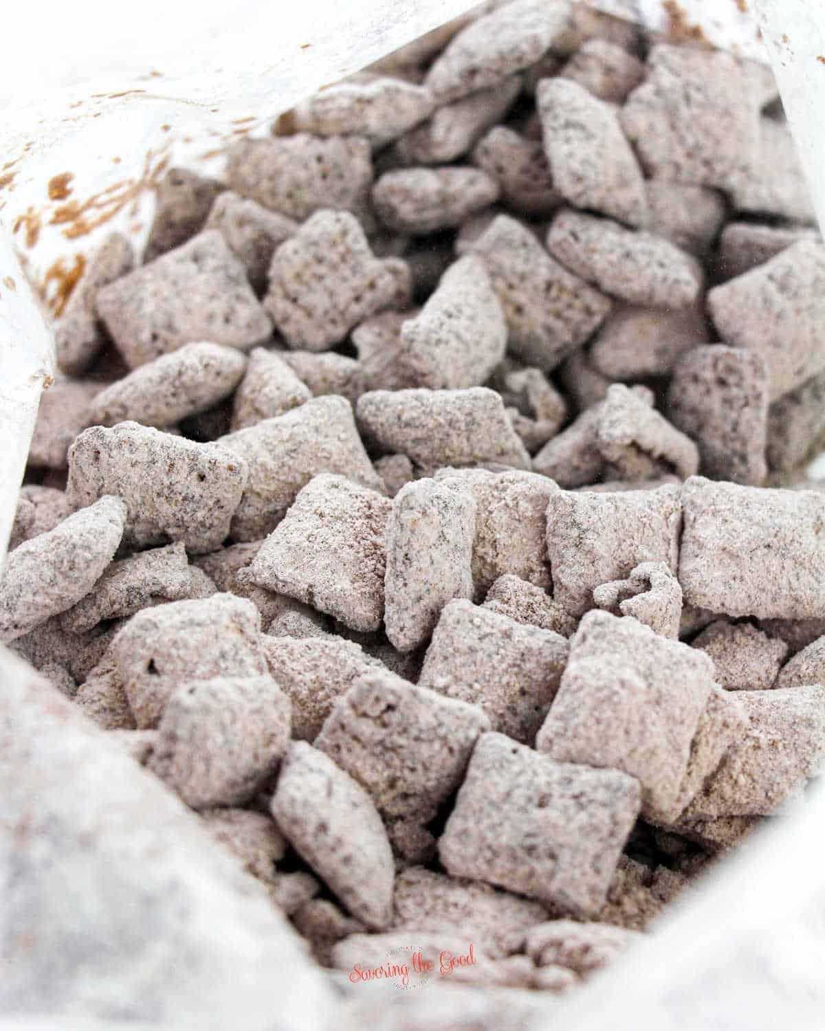 Christmas Puppy Chow after it has been shaken with powdered sugar and cocoa powder in a zip top bag