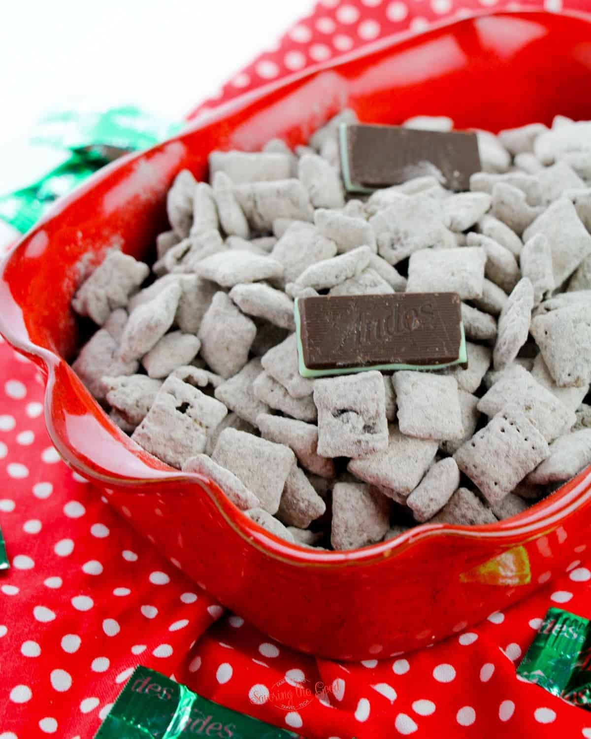 Christmas Puppy Chow with Andes candy as garnish on top in a bright red bowl