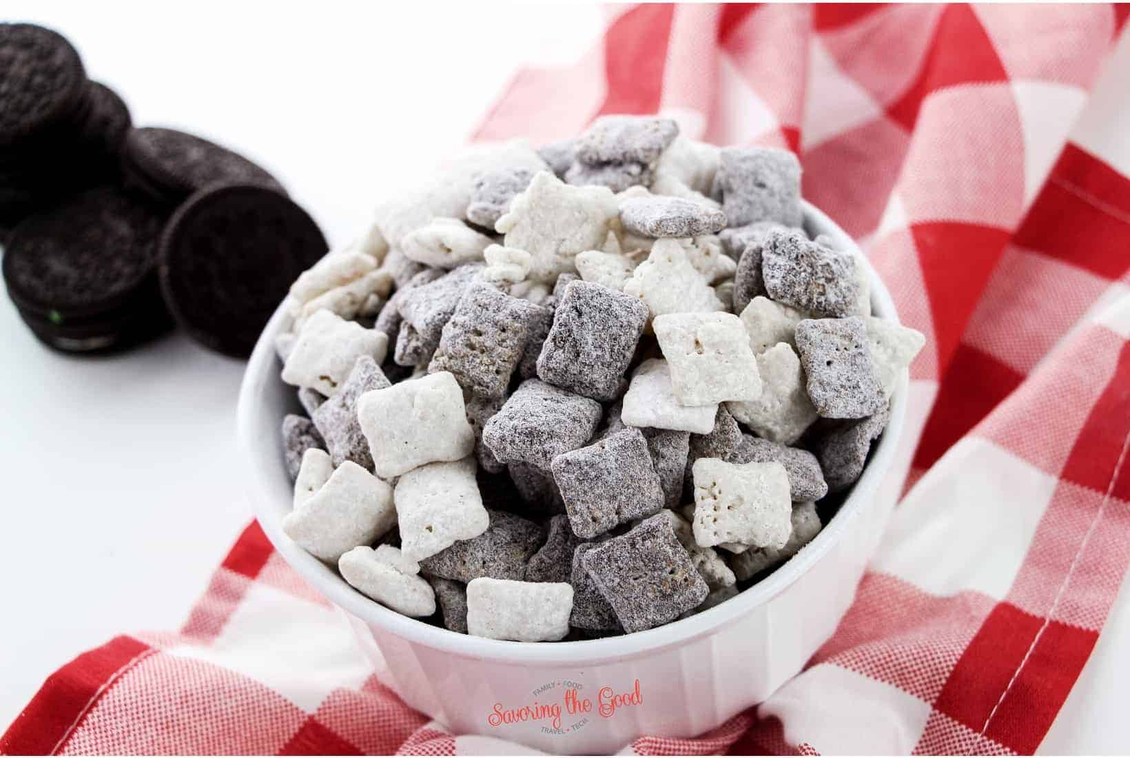 Cookies and cream muddy buddies in a white bowl on a red and white checked cloth