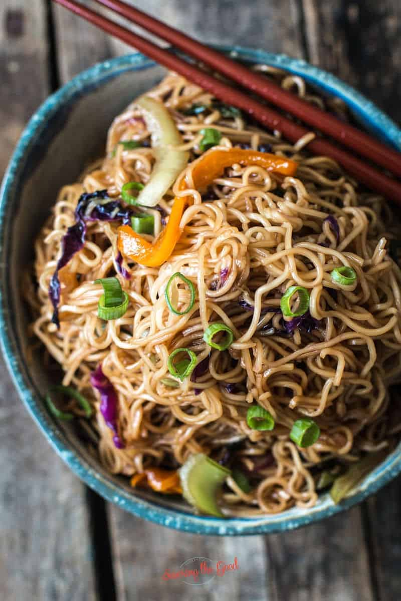 Ohana Noodles in an earthenware bowl and red chopsticks to the side