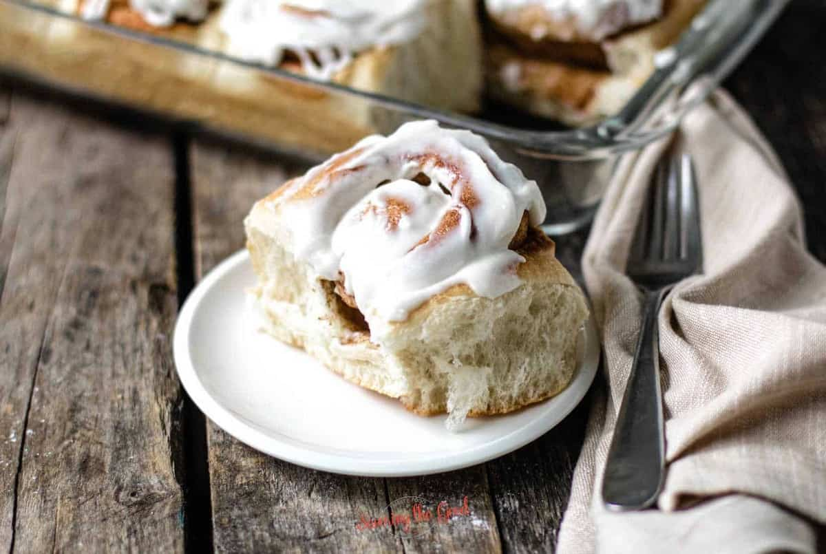 Rhodes Cinnamon Roll on a plate covered with icing on a small white plate