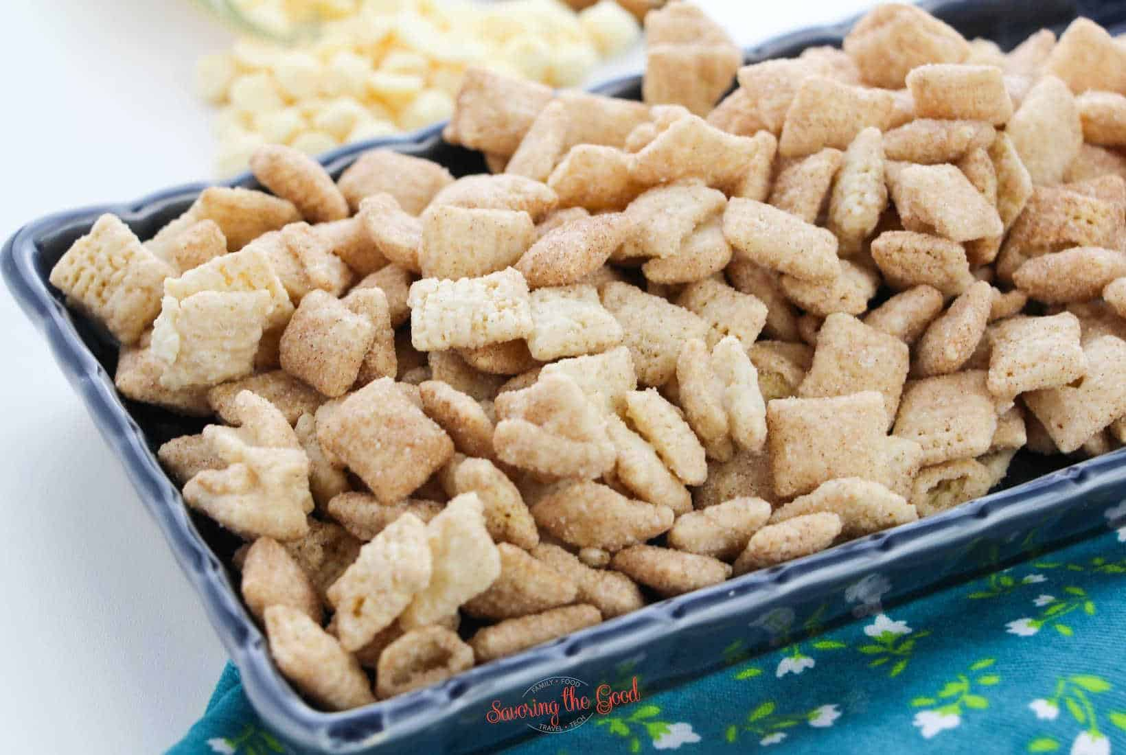 Snickerdoodle muddy buddies in a blue rectangle serving dish