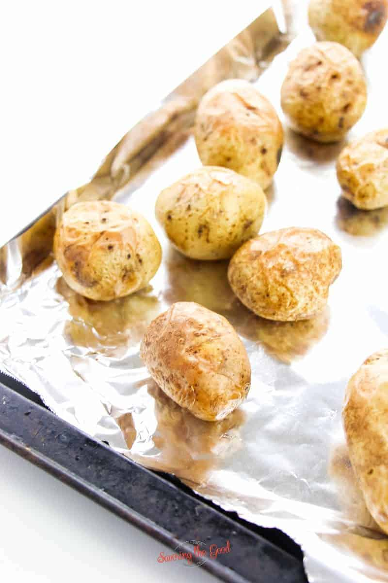 baked potatoes on a foil lined baking sheet