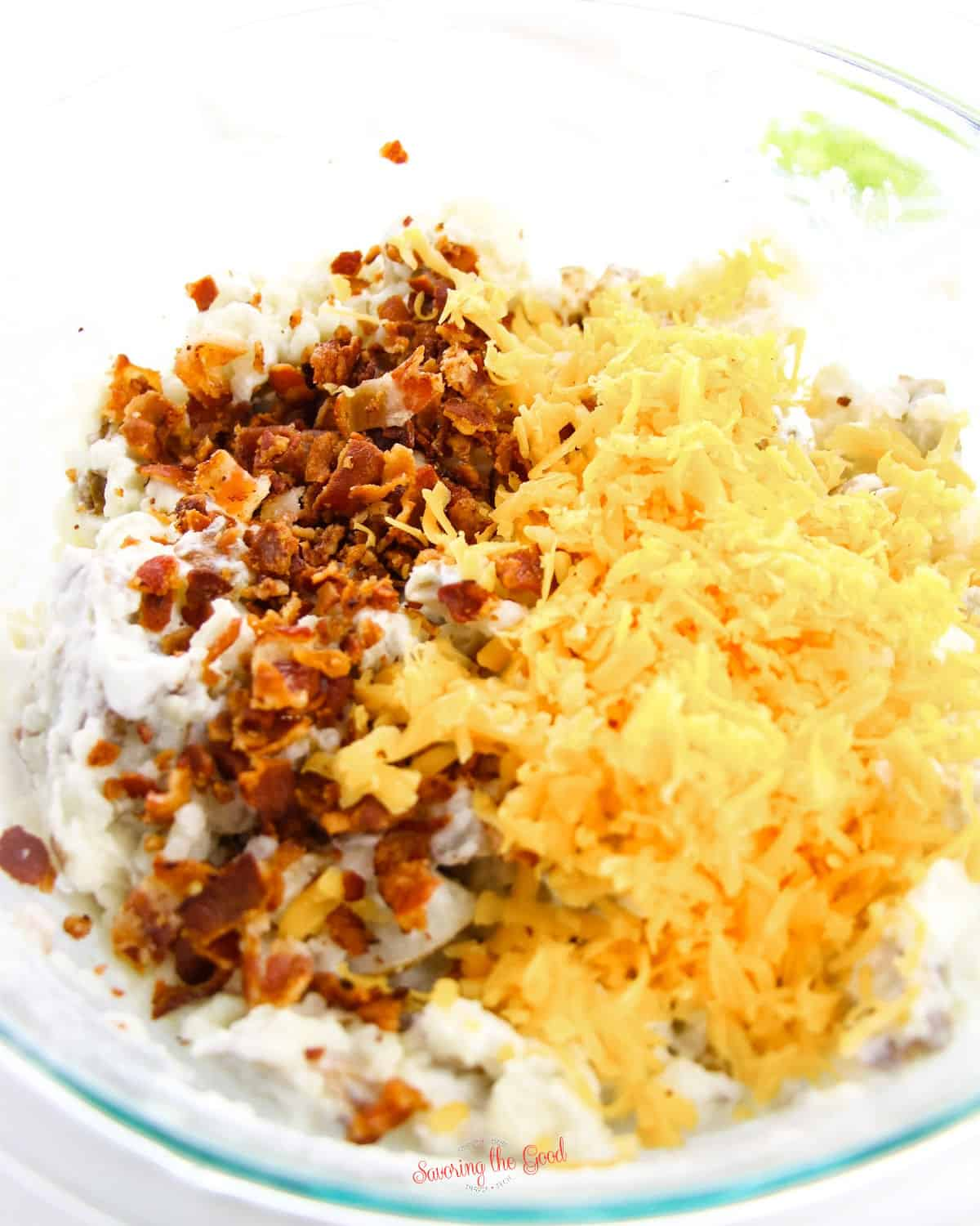cheese and bacon being mixed into patatoes