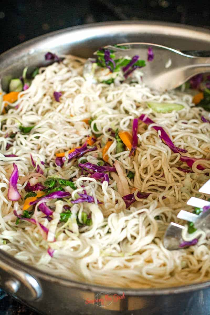 mixing the noodles and vegetables together, before the sauce is added