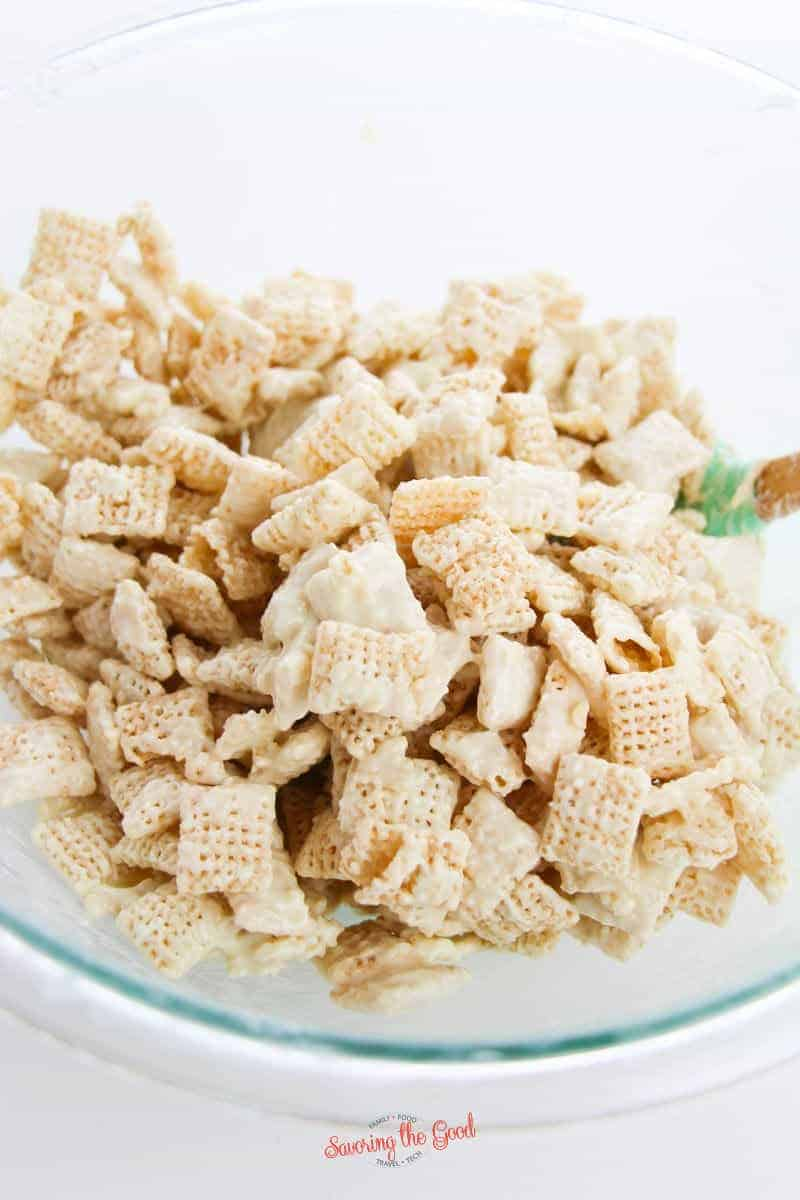 mixing white chocolate over chex for Snickerdoodle muddy buddies