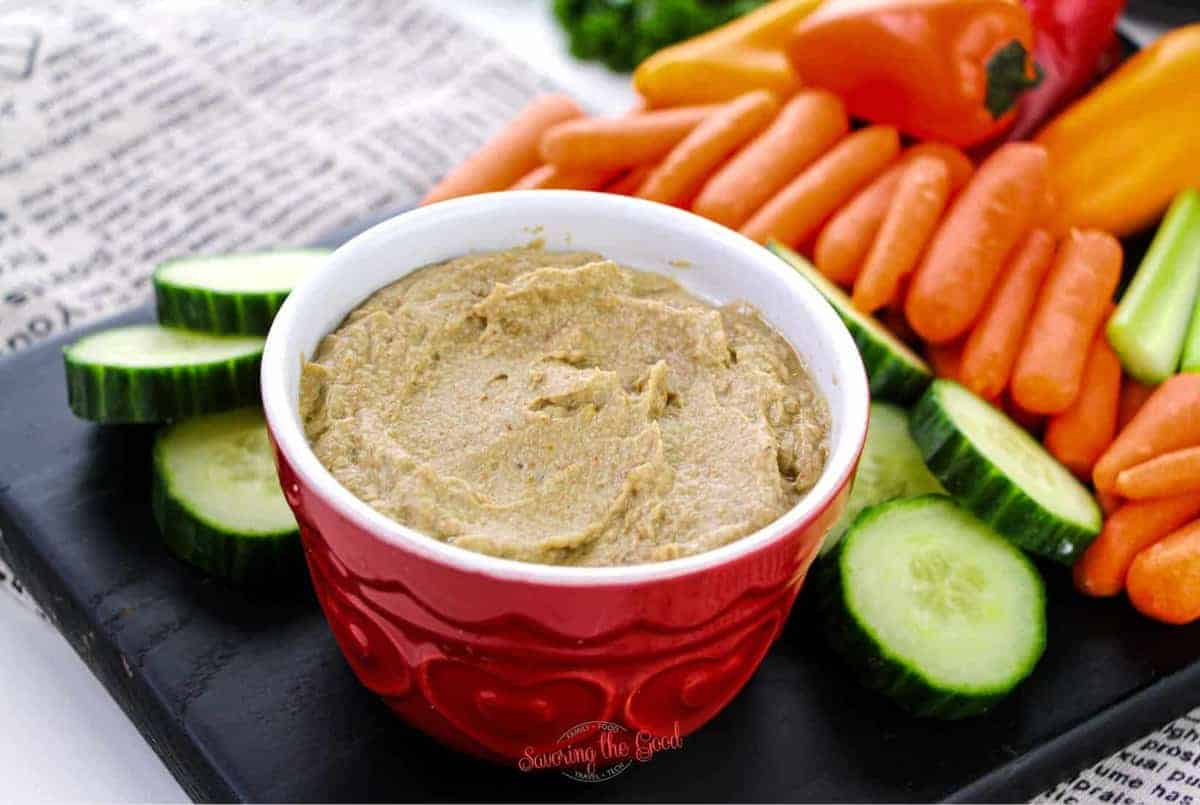 roasted Eggplant Dip in a red bowl on a black slate with fresh vegetables