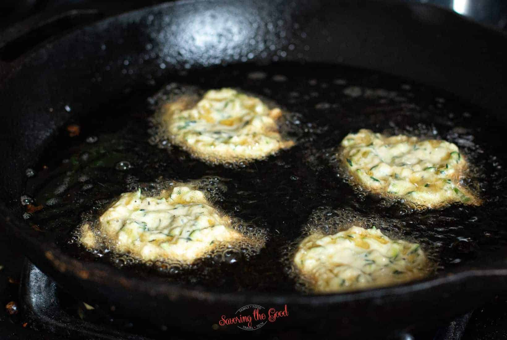 4 zucchini fritters in oil before they are flipped, still raw