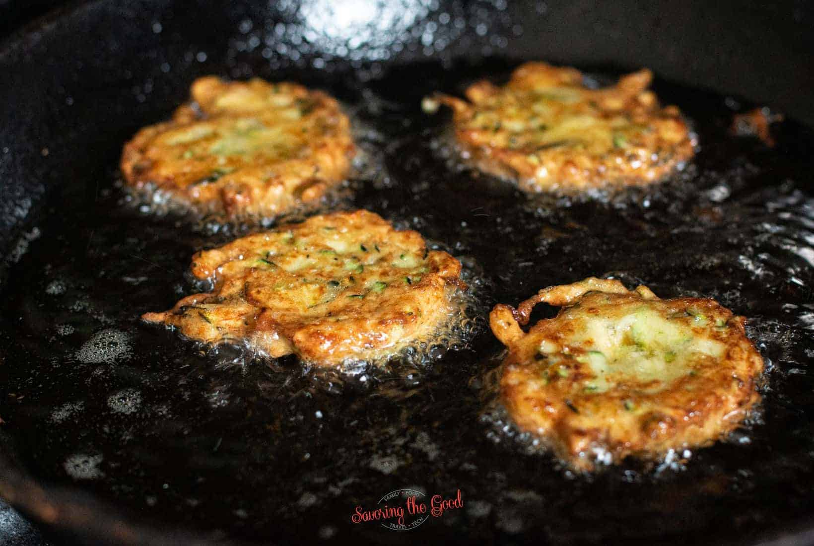 4 zucchini fritters pan frying in oil in a cast iron pan