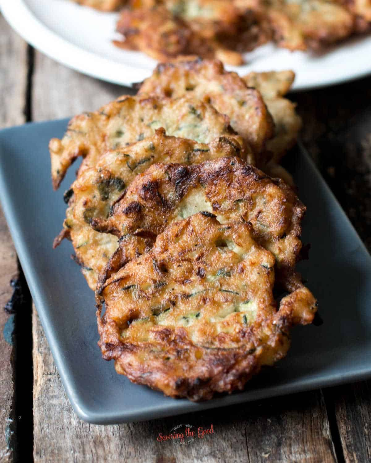 6 zucchini fritters on a grey rectangle plate
