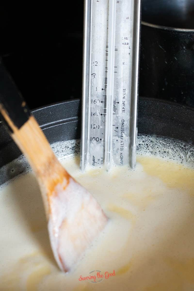 stiring icecream base with a bamboo spoon and a thermometor in the base