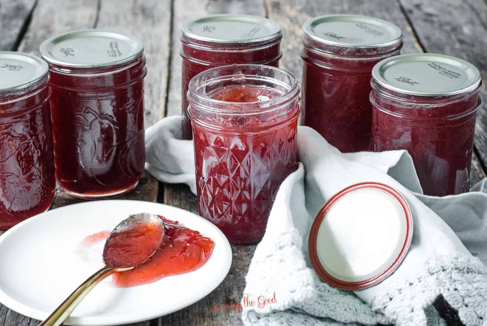 6 jelly jars of Rhubarb Jam, one open with a spoon pooling with jam on a white plate