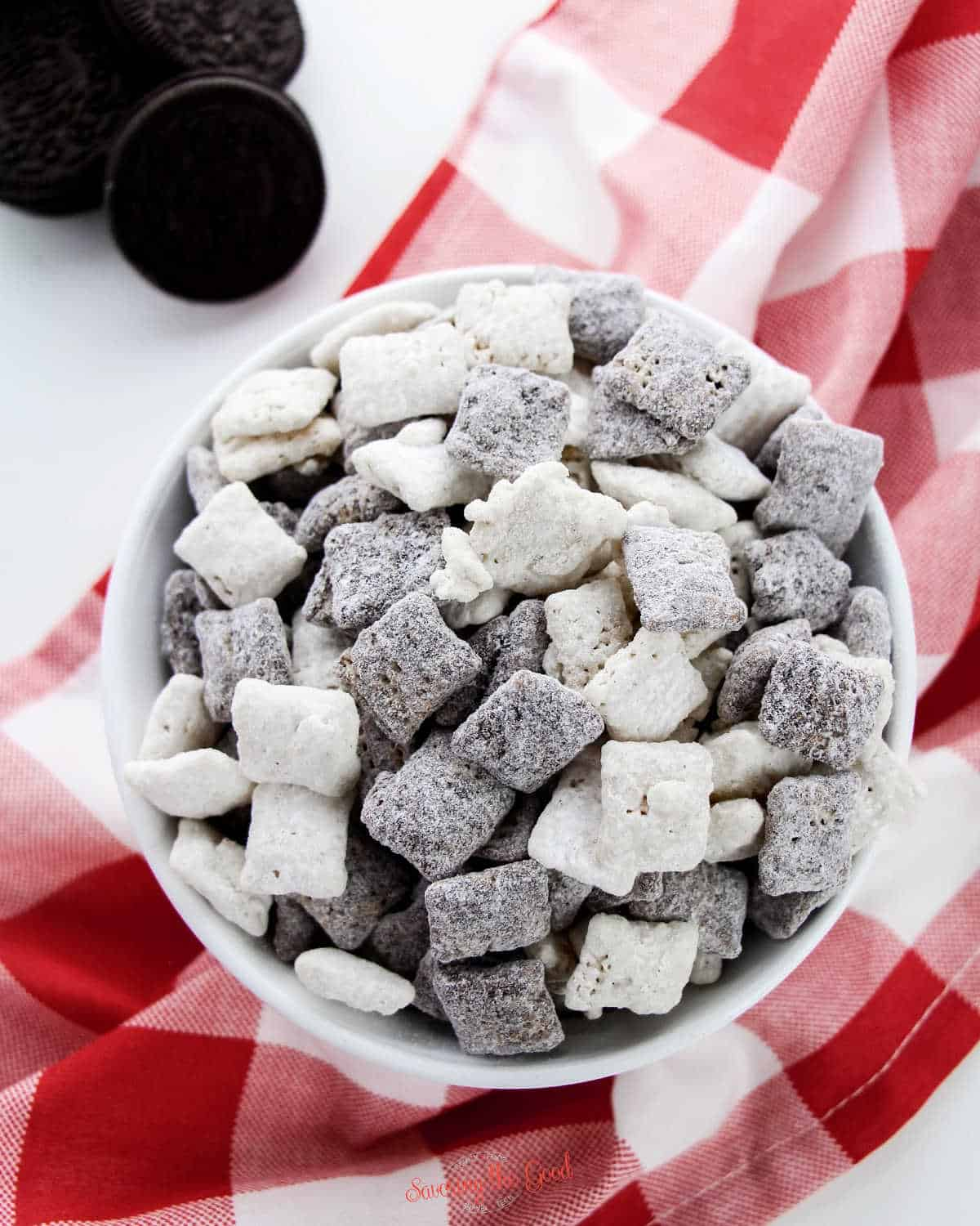 full bowl of Cookies and Cream Muddy Buddies on a red gingham table cloth covered table.