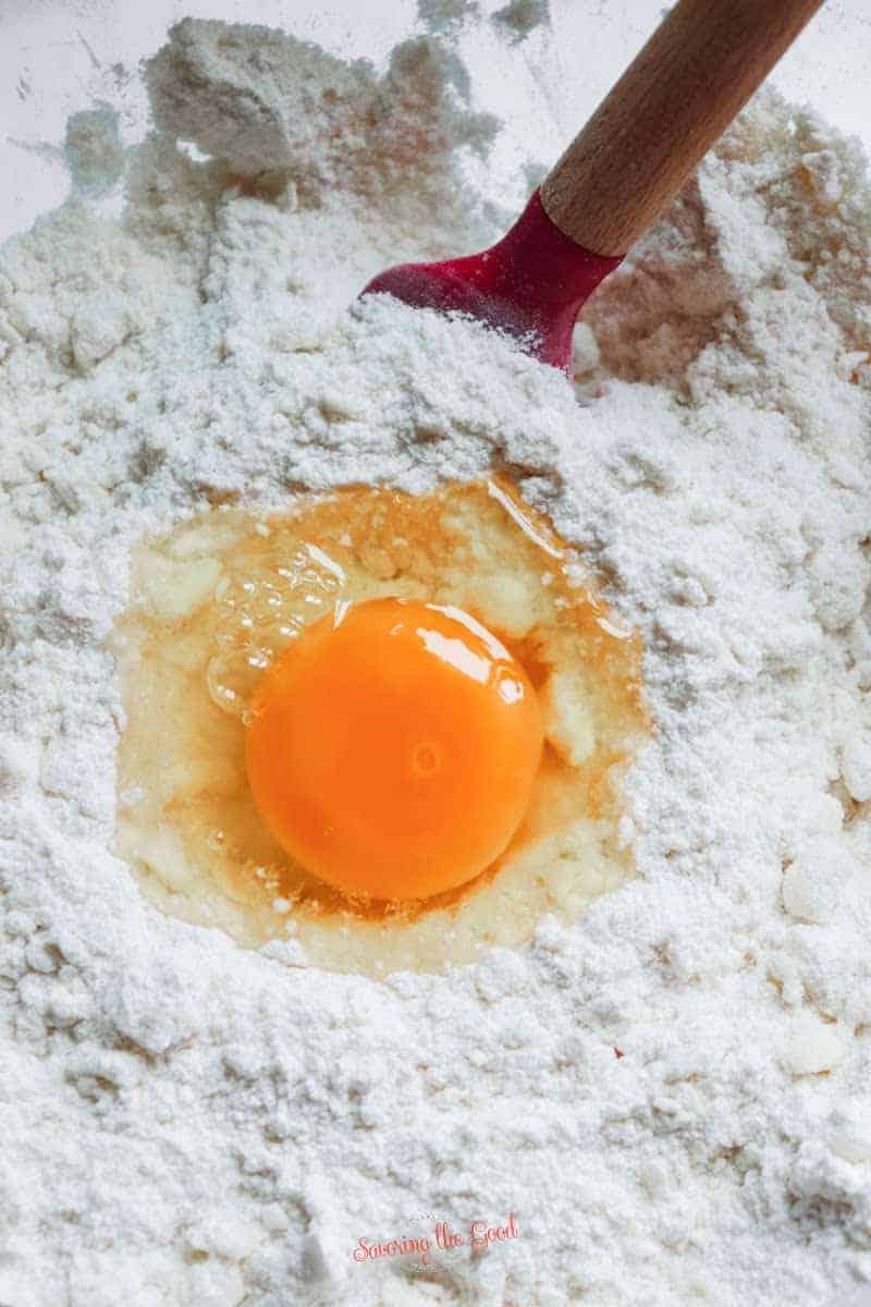 adding an egg to the dough