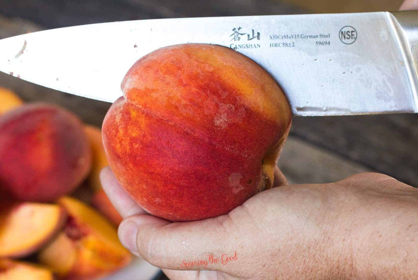 chef knife showing the propper technique for pitting a peach, slicing from end to end to free the flesh from the pit