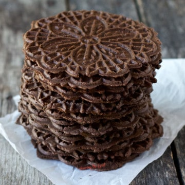 chocolate pizzelles stacked 7 high on a piece of white parchment paper