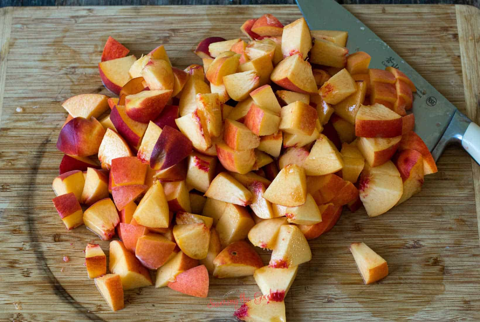 chopped peach with the skin still on them on a bamboo cutting board