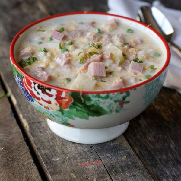 bowl of ham and potato soup with parsley garnish, sitting on a rustic wooden table, spoon and white napkin in the background