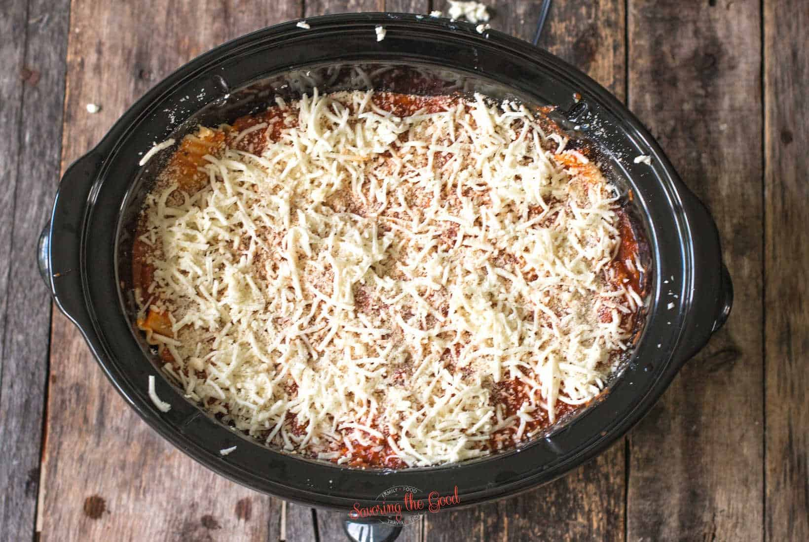 crockpot full of lasagna ready to be cooked, top down image