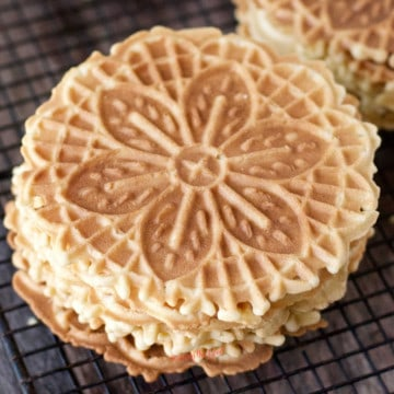 stack of 5 lemon pizzelle cookies on a cooling rack
