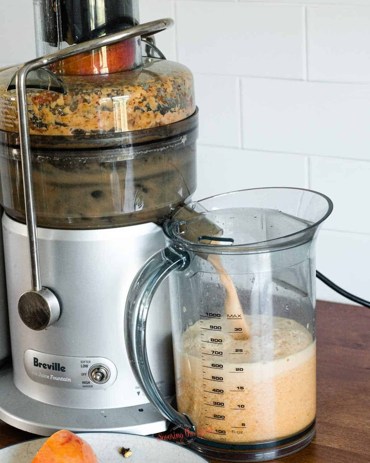 peaches being juiced in a breville fresh juice fountain, white tile backsplash in the background