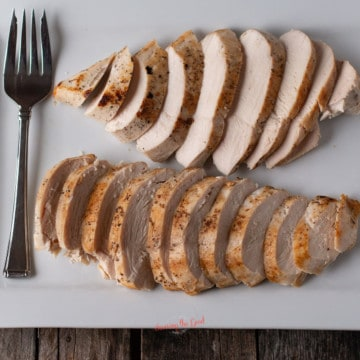 sous vide chicken breasts sliced and fanned out on a white platter