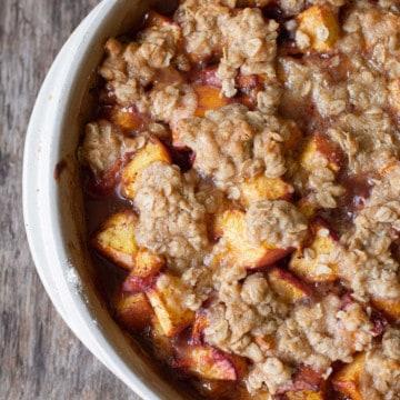 square image of peach crumble in a white stoneware dish