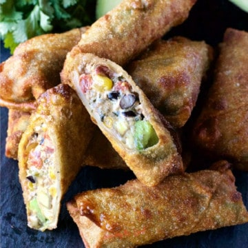 fried tex mex egg roll with beeg, cheese, corn, tomatoes, cream cheese black beans, cut open on the bias to show texture. Sitting on a pile of the rest of the the golden egg rolls
