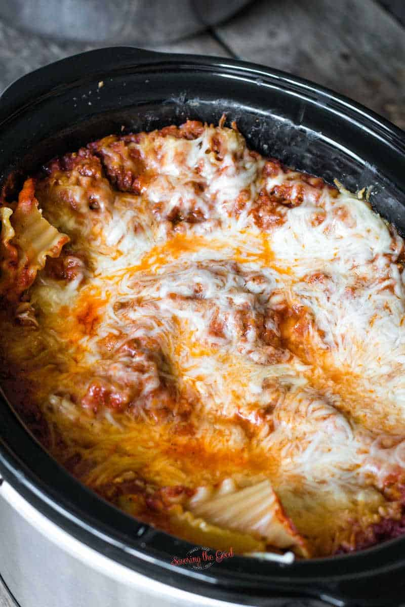 tight shot of the melted cheese over the lasagna in a crockpot
