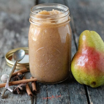 Pear butter in a glass canning jar with spices to the side and a whole pear to the right of the jar