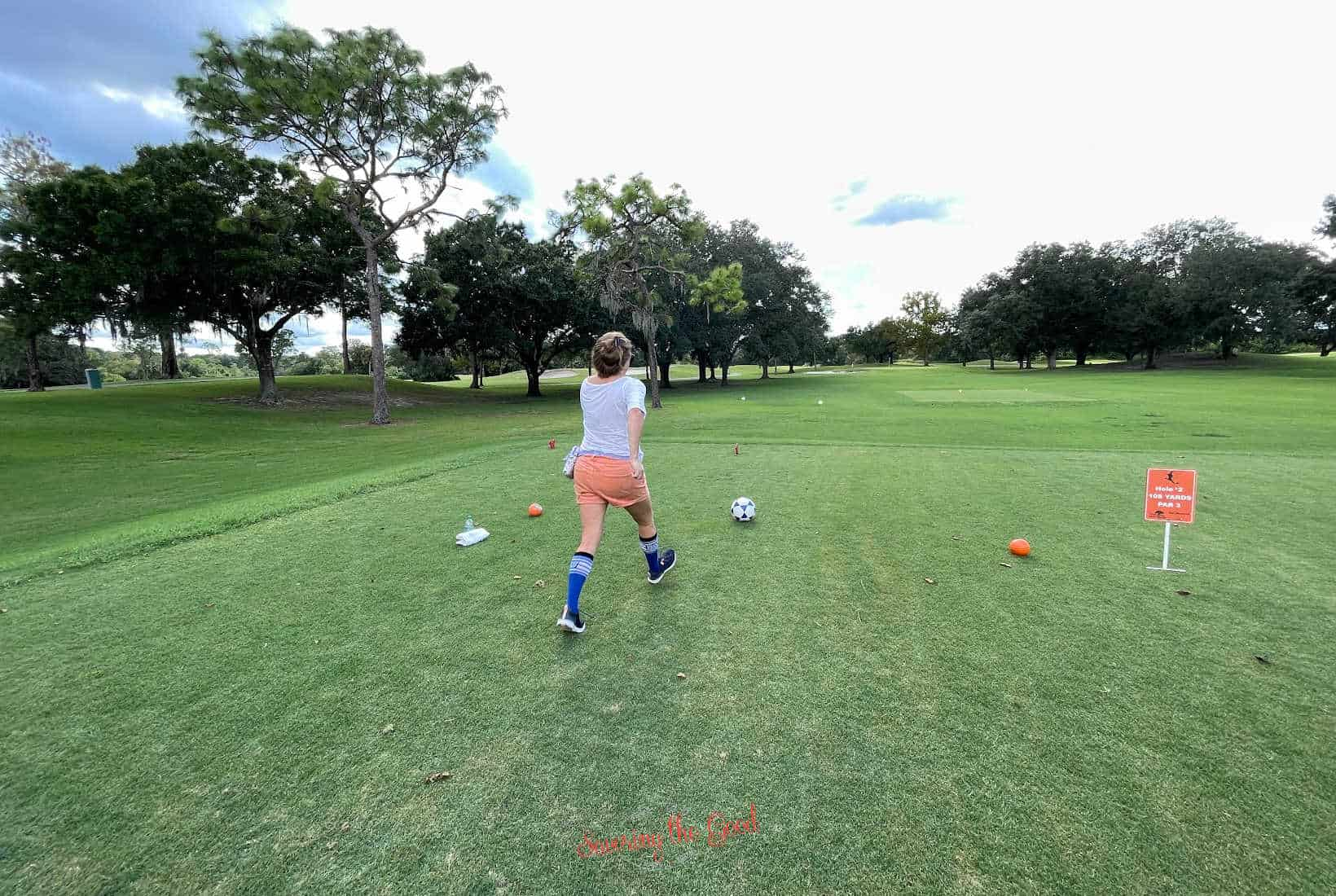 female in orange shorts and blue tall socks taking a running start to kick off for footgolf