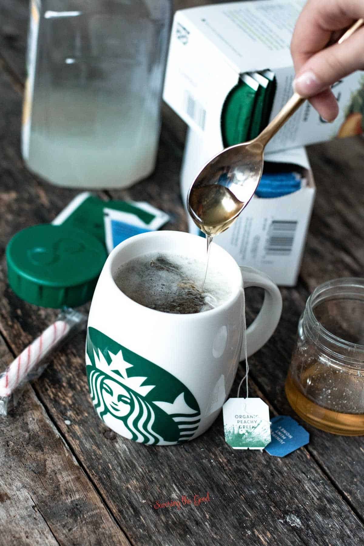 hand spooning honey into tea with starbucks medicine ball ingredients in the background