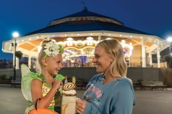 girl dressed as a fairy for Halloween next to a female holding a halloween themed milkshake in front of the carousel at Hersheypark
