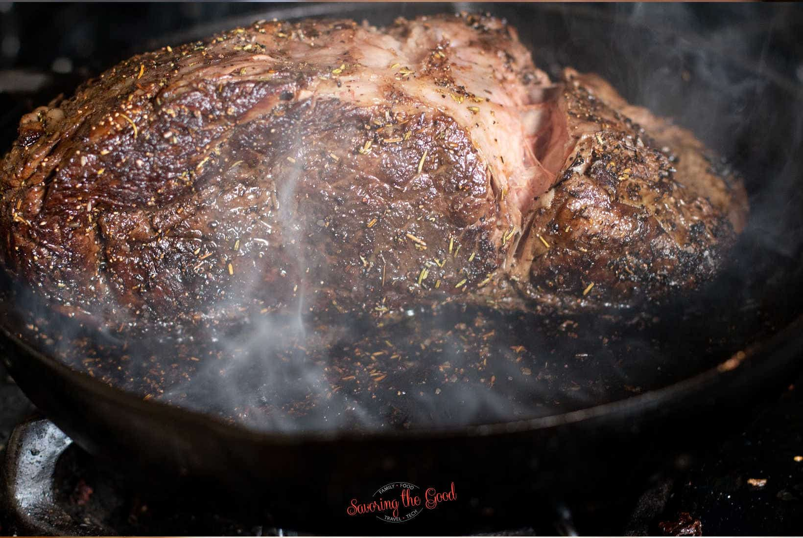 searing a piece of prime rib in a screaming hot cast iron skillet, smoke covers the meat