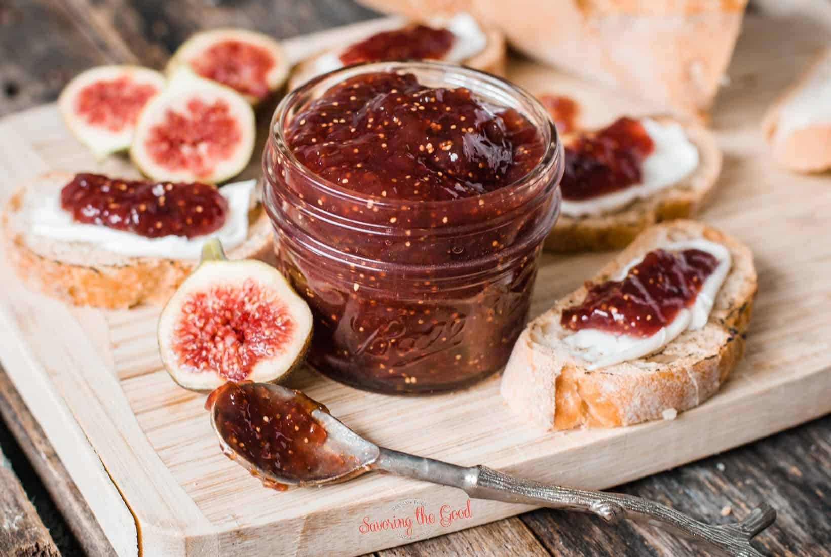 Fig Preserves in a 4 ounce mason jar with fresh figs, crustini and a spoon of jam
