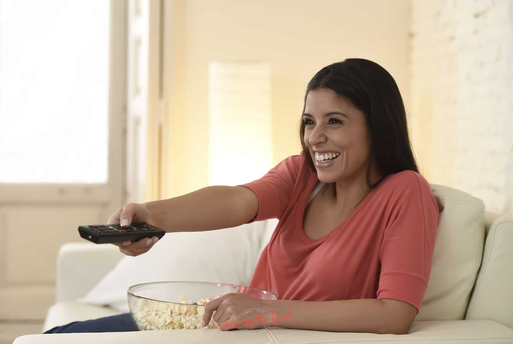 female in a chair with a remote control and a bowl of popcorn