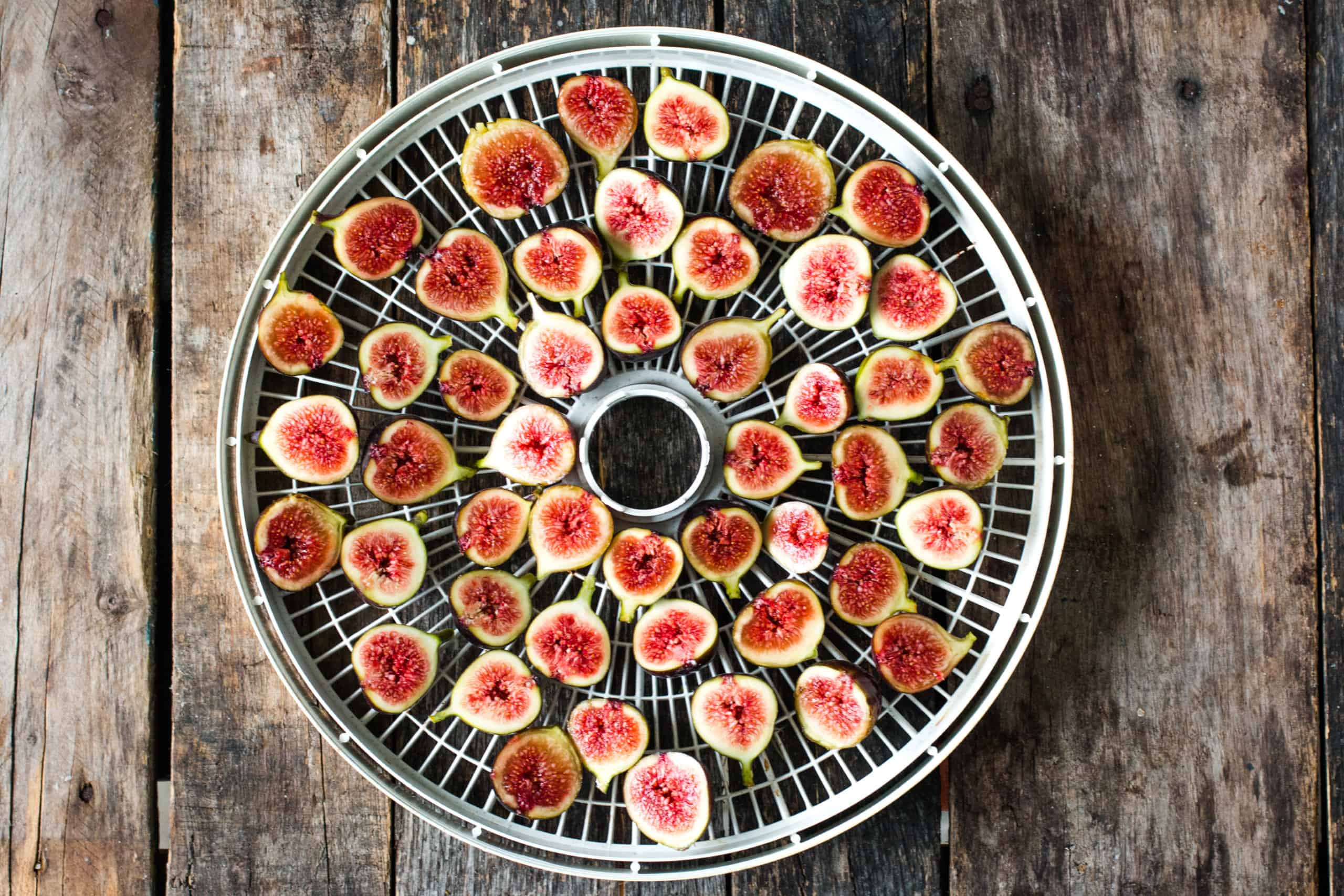 figs sliced in half paid out on a white cirgular dehydrating rack