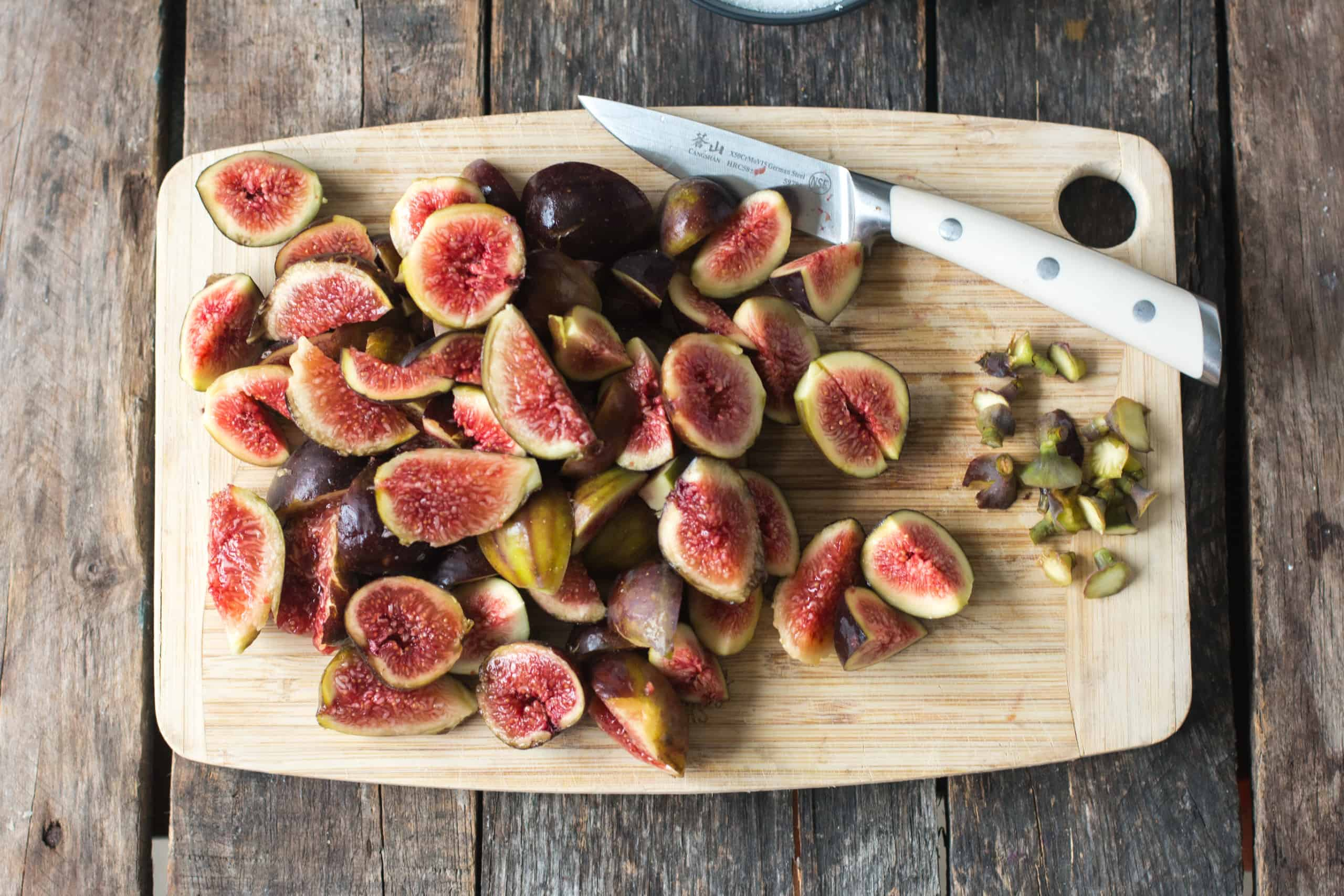 fresh figs being cut on a cutting board, removing the stem