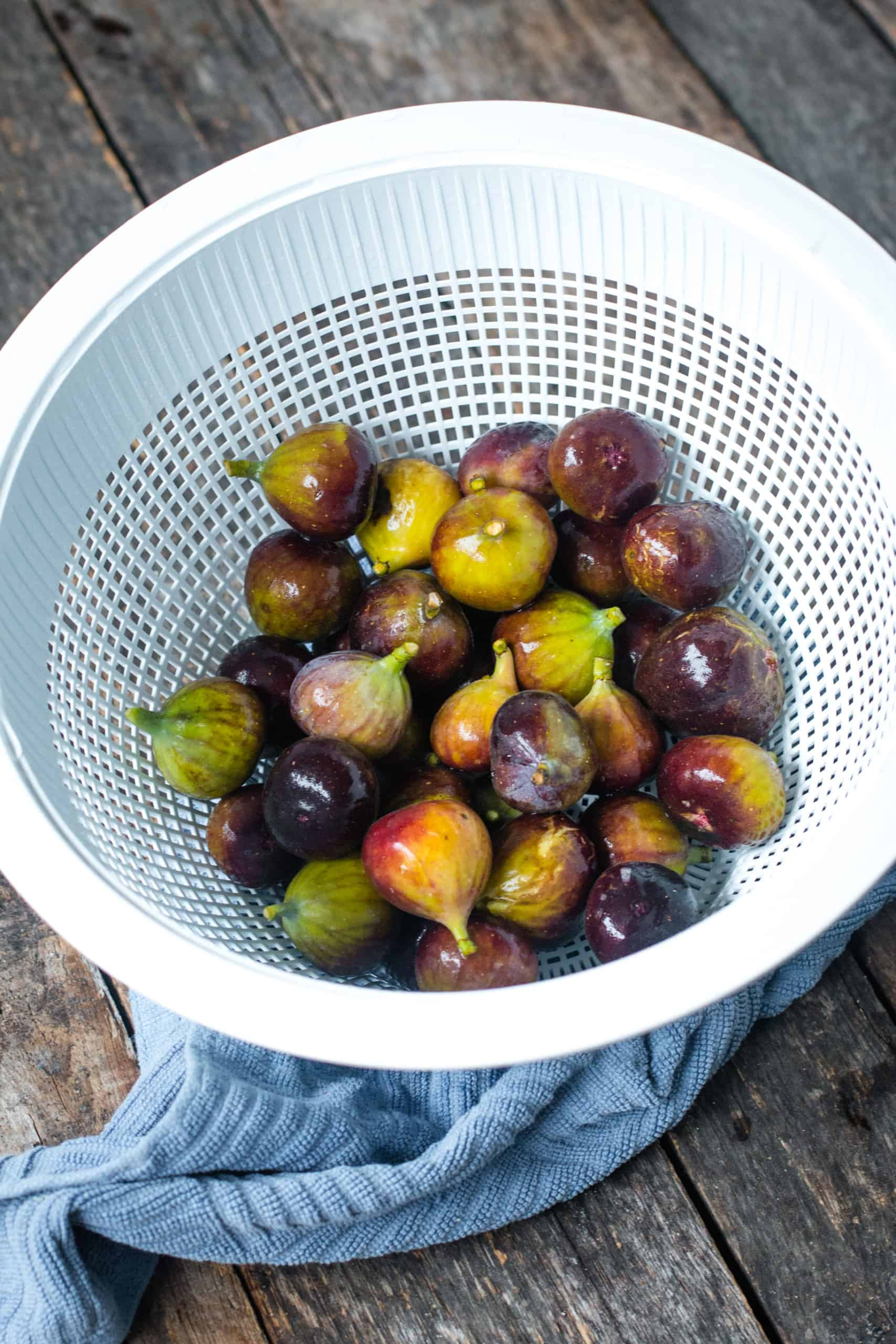 freshly washed fresh figs in a white colander