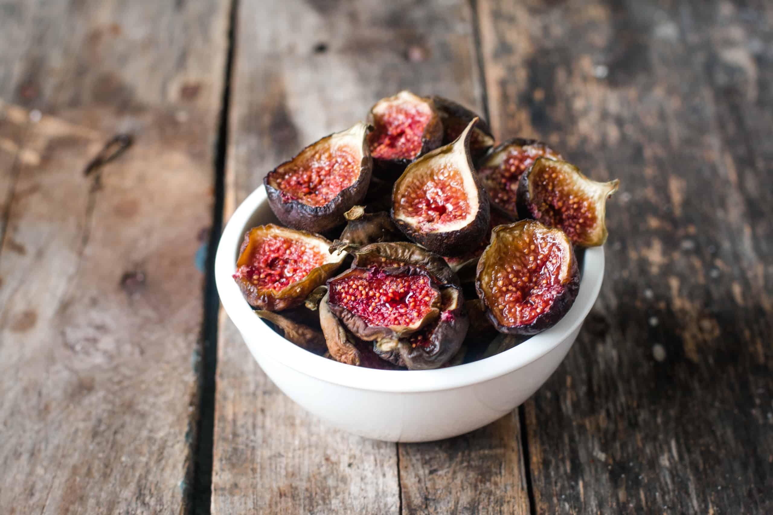 more than a dozen fig halves, drid in a small white bowl