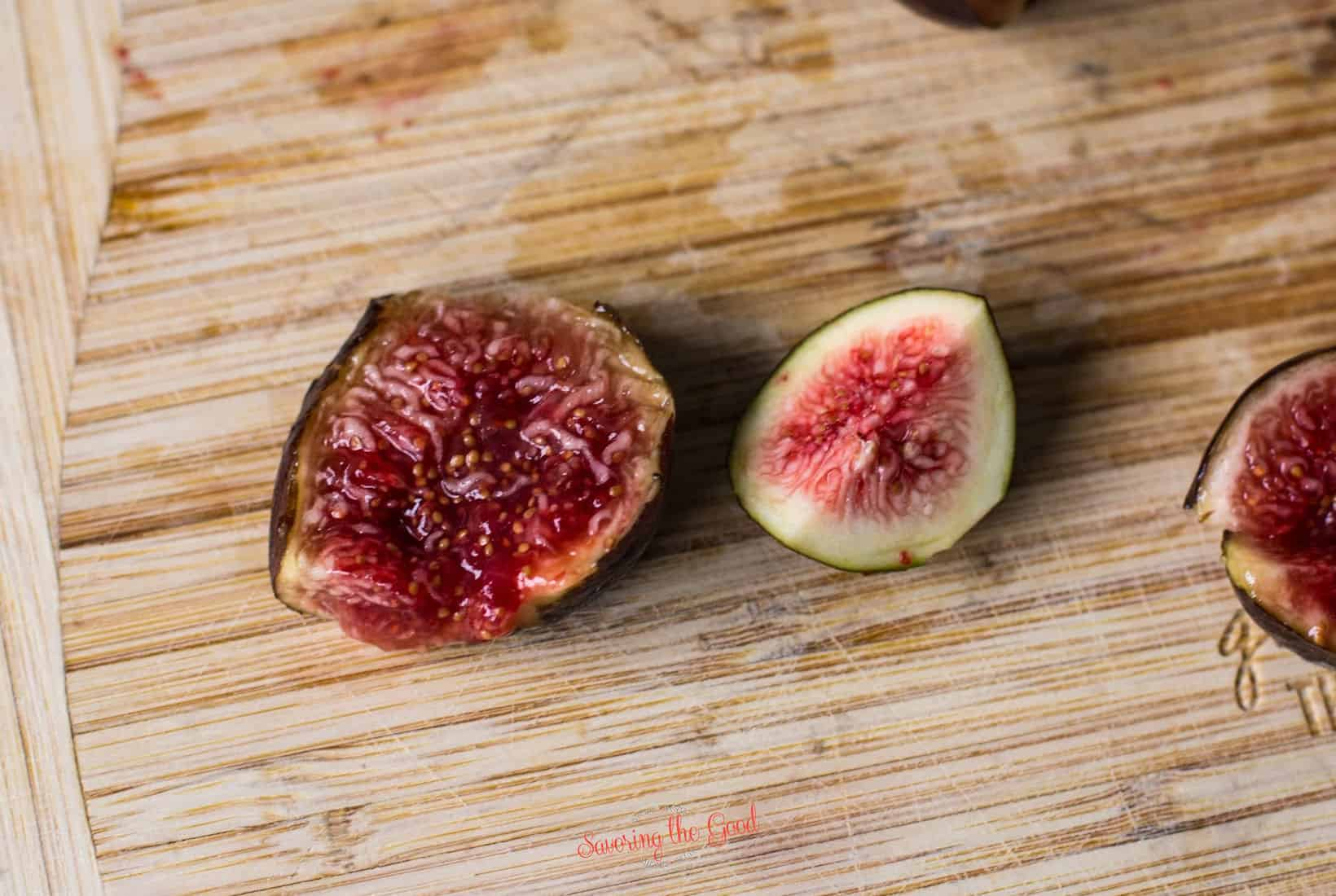 ripe fig open next to a less ripe fig cut open